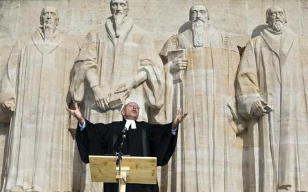 O pastor Philippe Reymond fala nas comemorações do 5° centenário de Calvino, à frente do muro dos reformadores em Genebra. Salvatore di Nolfi, Keystone.