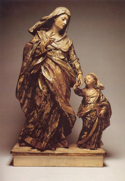 Sant'Ana, mãe da Santíssima Virgem Maria e esposa de São Joaquim, vem sempre acompanhada de sua filha. Nesta representação, as duas caminham de mãos dadas e Nossa Senhora segura seu livro. Acervo: Imaginária. http://www.mas.ufba.br/obra.asp?peccodigo=63