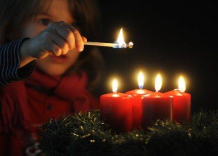 ILLUSTRATION - Ein Mädchen hält ein entzündetes Streichholz vor vier brennenden Kerzen auf einem Adventskranz, aufgenommen am 25.11.2010 in Straubing (Niederbayern). Seit Mitte des 19. Jahrhunderts gibt es in Deutschland Adventskränze. Sie gelten als Symbol für die vorweihnachtliche Zeit. Foto: Armin Weigel dpa/lby